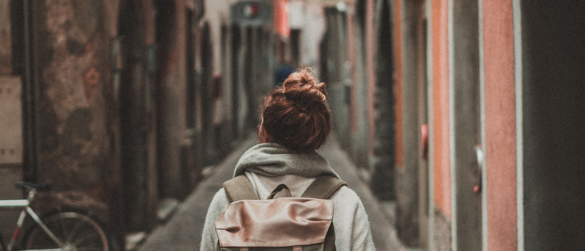 woman walking on street surrounded by buildings