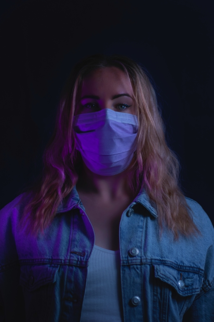 woman in purple denim jacket with white mask