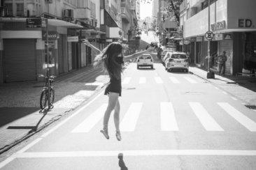 grayscale photo of woman walking on pedestrian lane