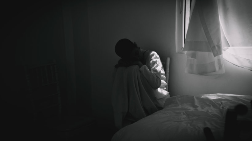 person in gray hoodie sitting on bed