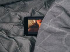 black Android smartphone on gray bed sheet