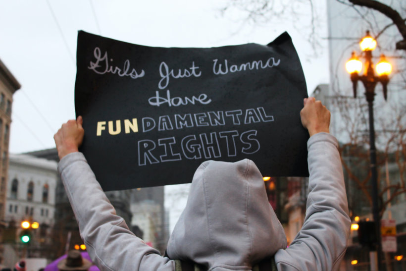 person in gray hooded jacket holding black sign