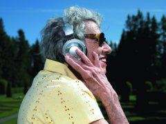 elderly woman listening to headphones. exterior day park setting
