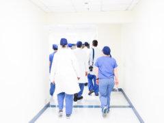 group of doctors walking on hospital hallway
