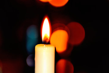 white candle in bokeh photography
