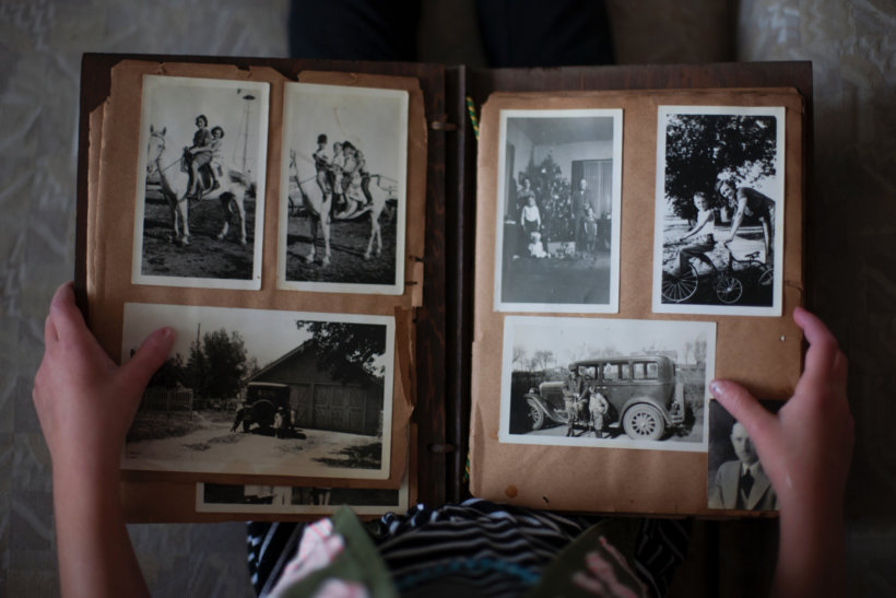 person opening photo album displaying grayscale photos