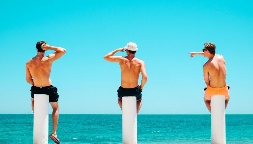 three men's sitting on white concrete bollard near body of water during daytime