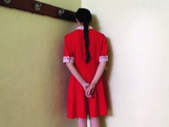 Woman in red dress standing in the corner